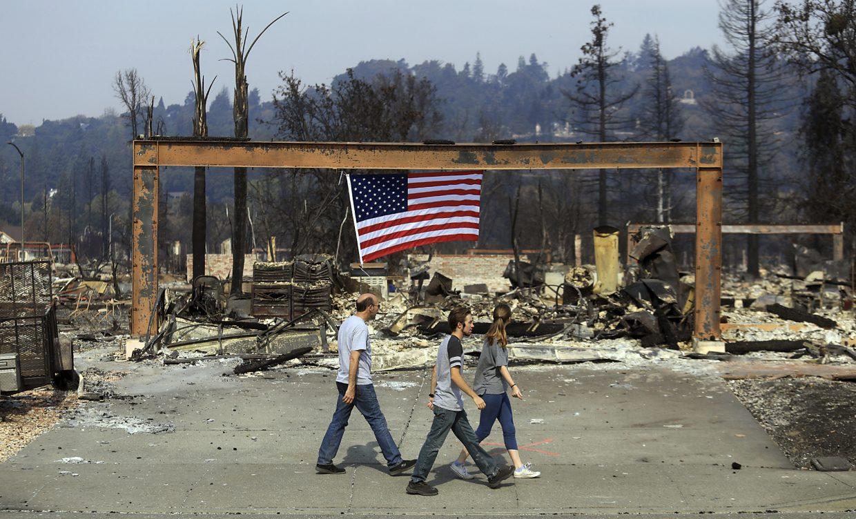 From left, Rick Olcese, Ty Knapp and Ariana Olcese search for the Olcese family cats in the Larkfield neighborhood, Monday Oct. 16, 2017, near Santa Rosa, Calif. Calm winds gave an advantage to firefighters trying to tame the flames of deadly wildfires on Monday.