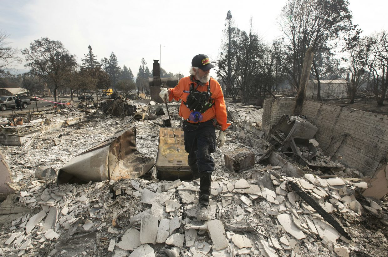 J. Petrocelli of the Alameda County Sheriff's Office Search and Rescue walks through the burned out remains of a home while searching the Coffey Park area Tuesday, Oct. 17, 2017, in Santa Rosa, Calif. A massive wildfire swept through the area last week destroying thousands of housing and business and taking the lives of more than two dozen people.