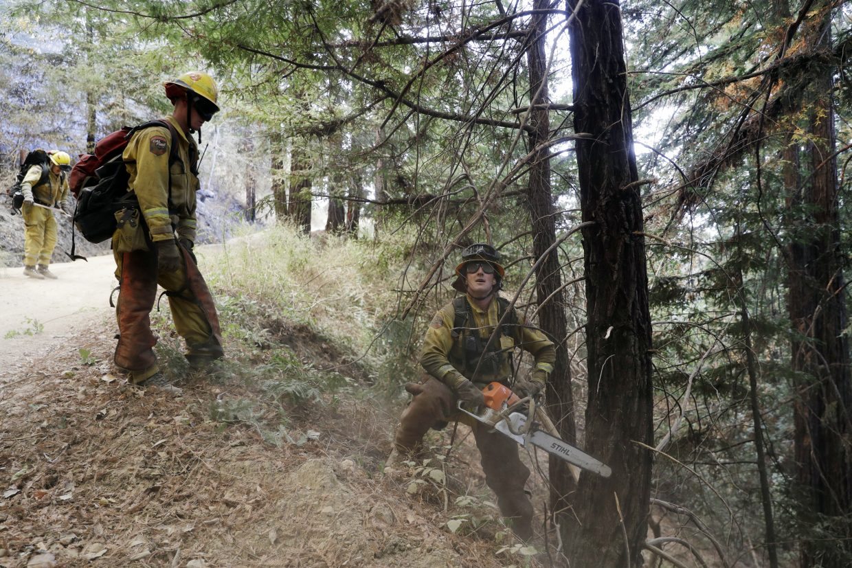 Crews chop down branches and trees as they battle a wildfire Tuesday, Oct. 17, 2017, near Boulder Creek, Calif.