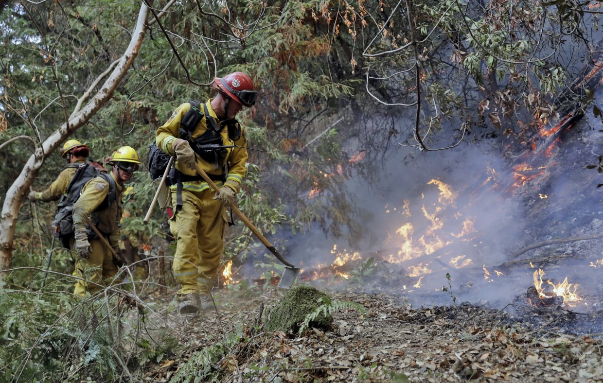 Fire crews build a containment line as they battle a wildfire Tuesday, Oct. 17, 2017, near Boulder Creek, Calif.