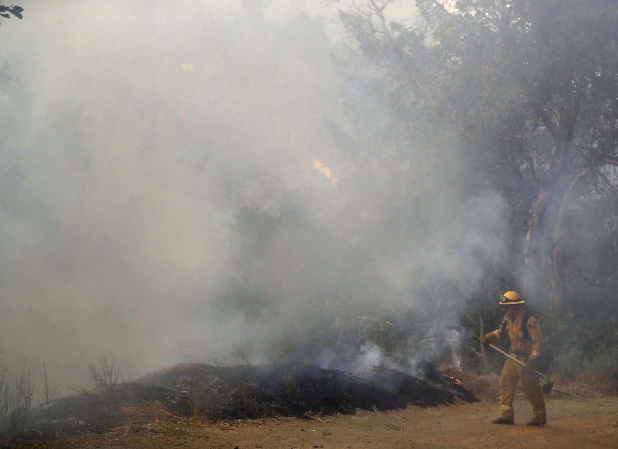 A firefighter is covered in smoke as he monitors a wildfire along a fire road Tuesday, Oct. 17, 2017, near Boulder Creek , Calif.