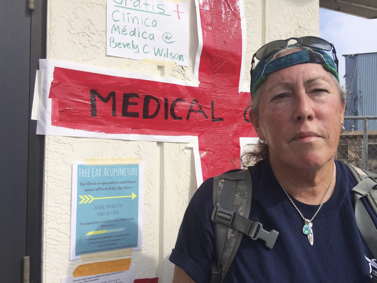 Jen Nadeau, a retired firefighter-EMT from Vallejo Fire is shown at a shelter in Petaluma, Calif., Tuesday, Oct. 17, 2017. Nadeau has been volunteering at the shelter for fire evacuees in Petaluma every day since the fires broke out, helping people cope with anxiety and assessing their health needs.