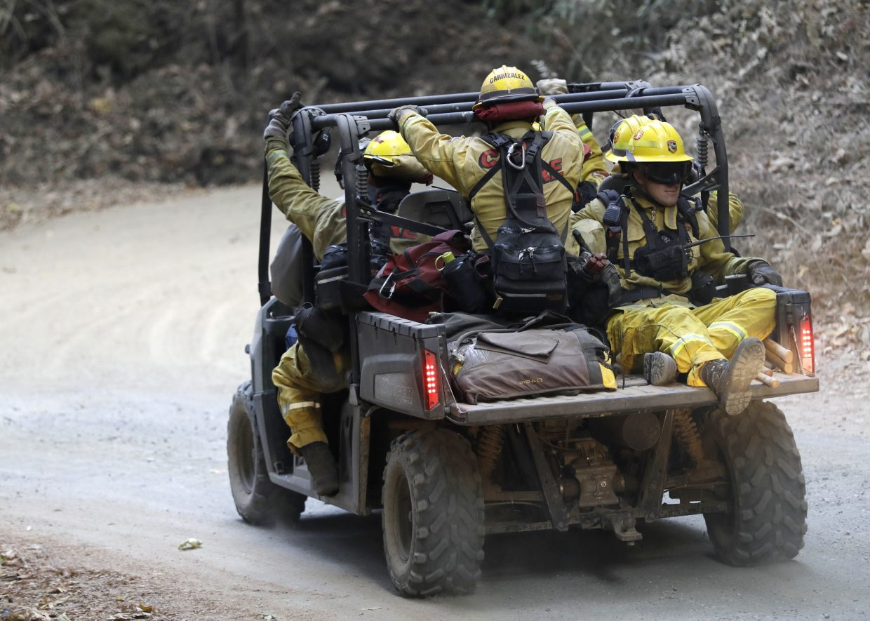 Fire crews are driven up a fire road en route to battling a wildfire Tuesday, Oct. 17, 2017, near Boulder Creek, Calif.