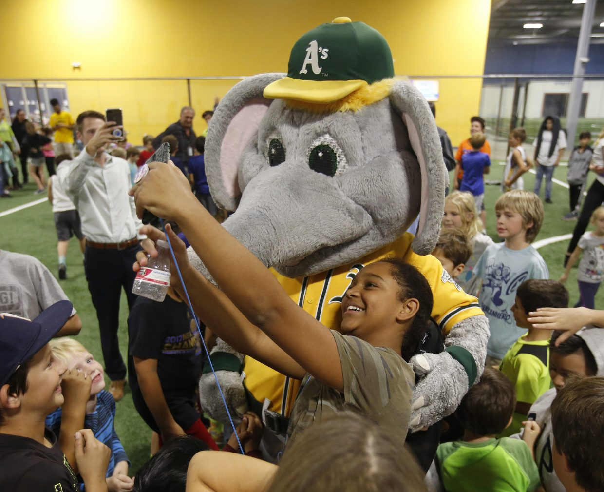 Deja Jones, 12, takes a selfie with Stomper, the mascot of the Oakland A's Major League Baseball team at the Epicenter sports complex, Tuesday, Oct. 17, 2017, in Santa Rosa, Calif. Stomper and A's catcher Bruce Maxwell visited the center and brought items for the kids at the center that has opened it's doors for the area children affected by the recent wildfires.