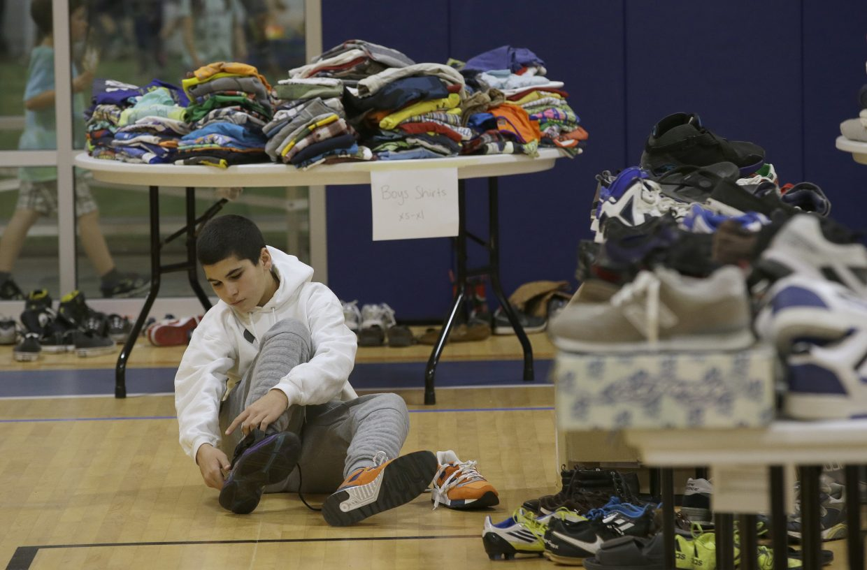 Mehdi Latrache tries on shoes at a donation center for victims of the recent wildfires, Tuesday, Oct. 17, 2017, in Santa Rosa, Calif. Latrache and his family lost their Coffey Park home a week ago as a massive wildfire swept through the area.