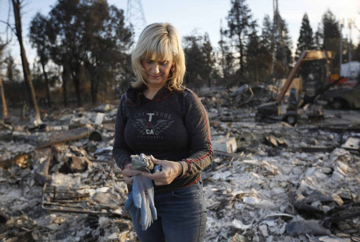 Debbie Wolfe stares at the broken figurine, she found in the burned ruins of her home Tuesday, Oct. 17, 2017, in Santa Rosa, Calif. A massive deadly wildfire swept through the area last week destroying thousands of housing and business.