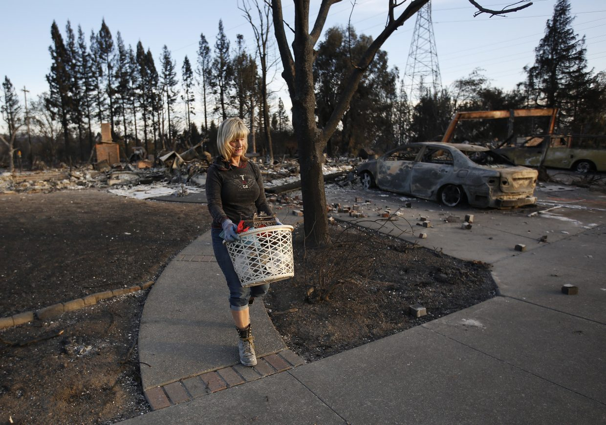Debbie Wolfe uses a laundry basket to carry the few things she found that were destroyed in the burned ruins of her home of 30 years, Tuesday, Oct. 17, 2017, in Santa Rosa, Calif. A massive deadly wildfire swept through the area last week destroying thousands of housing and business.