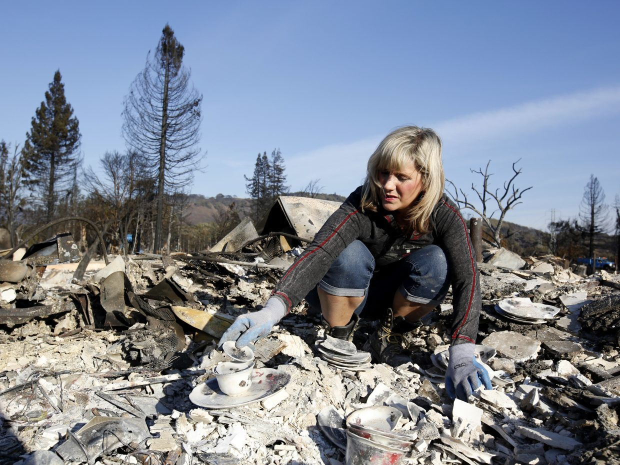 Debbie Wolfe stacks some china to take with her, that once belonged to her grandmother, found in the burned ruins of her home, Tuesday, Oct. 17, 2017, in Santa Rosa, Calif. A massive deadly wildfire swept through the area last week destroying thousands of housing and business.
