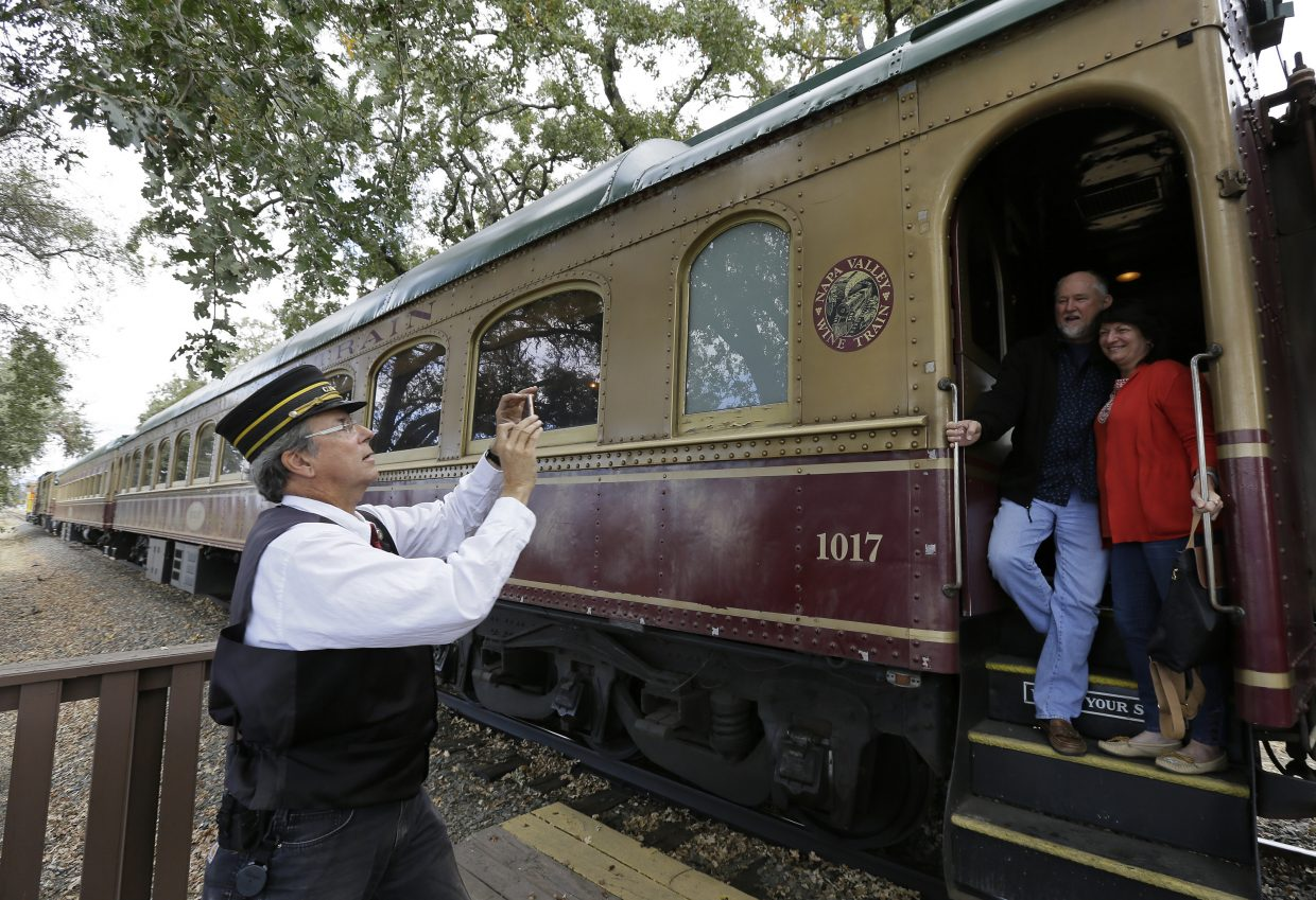 Napa Valley Wine Train conductor Michael Williams takes pictures of a couple as they leave the train to tour the Grgich Hills Estate winery Thursday, Oct. 19, 2017, in Rutherford, Calif. The winery and train resumed operation this week after last week's wildfires.