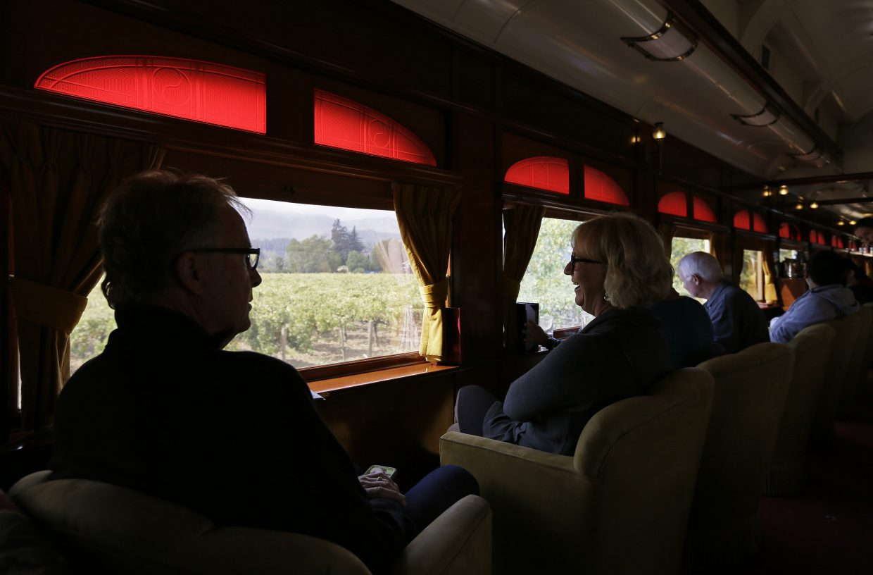 People enjoy the view of vineyards from the lounge car while riding the Napa Valley Wine Train, Thursday, Oct. 19, 2017, in Oakville, Calif. The train resumed its runs this week after last week's wildfires.
