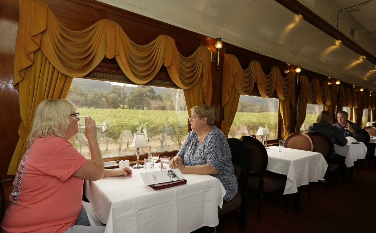 Julie Norris, left, of Florida, drinks a glass of wine while riding the Napa Valley Wine Train with Paula Anderson, of Connecticut, Thursday, Oct. 19, 2017, in Oakville, Calif. The train resumed its runs this week after last week's wildfires. The wildfires that have devastated California this month caused at least $1 billion in damage to insured property, officials said Thursday, as authorities raised the number of homes and other buildings destroyed to nearly 7,000.