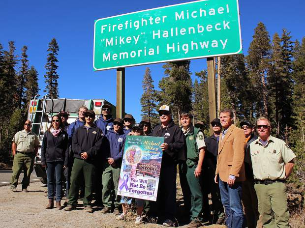 "People pose for a photo by the new ""Firefighter Michael 'Mikey' Hallenbeck Memorial Highway"" signs."