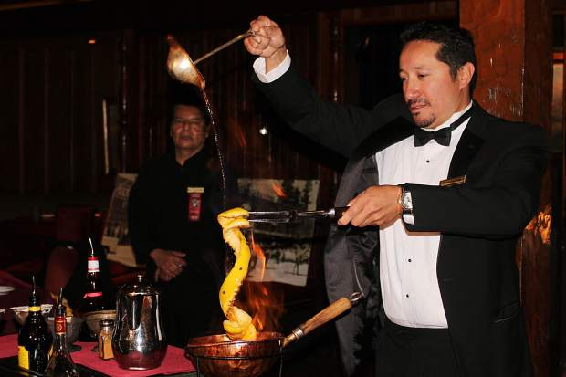 Maître d' Ozzie Sanchez prepares a Cafe Diablo, which is flavored with clove-studded orange and lemon peels, Grand Marnier, brandy, and Kahlua with a hint of coffee.