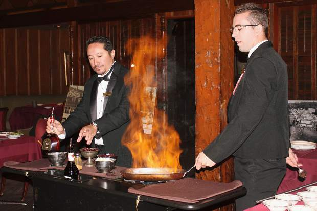 The staff at the Sage Room flambés Cherries Jubilee, one of the many dishes at the steakhouse that is prepared tableside.