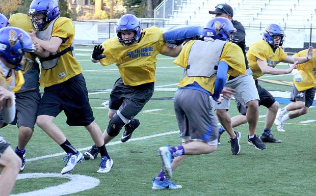 South Tahoe senior Logan Langemeier fights off a block from head coach Louis Franklin Tuesday during practice.