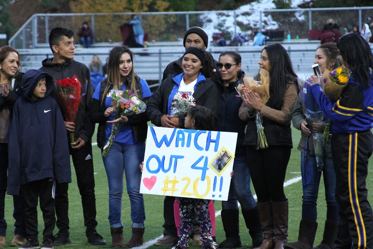 South Tahoe senior Lulu Gutierrez stands with her family Friday night at halftime.