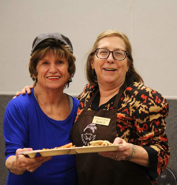 Carol Olivas (left) and Kathi Olsen hold up a tray of food.