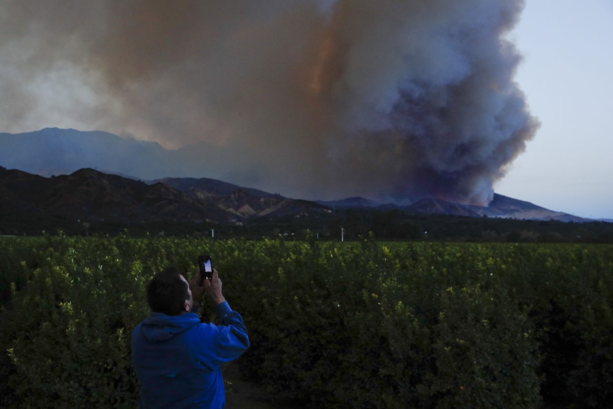 Lupe Robles uses his phone to take pictures of a huge plume of smoke from a wildfire in Santa Paula, Calif., Thursday, Dec. 7, 2017.