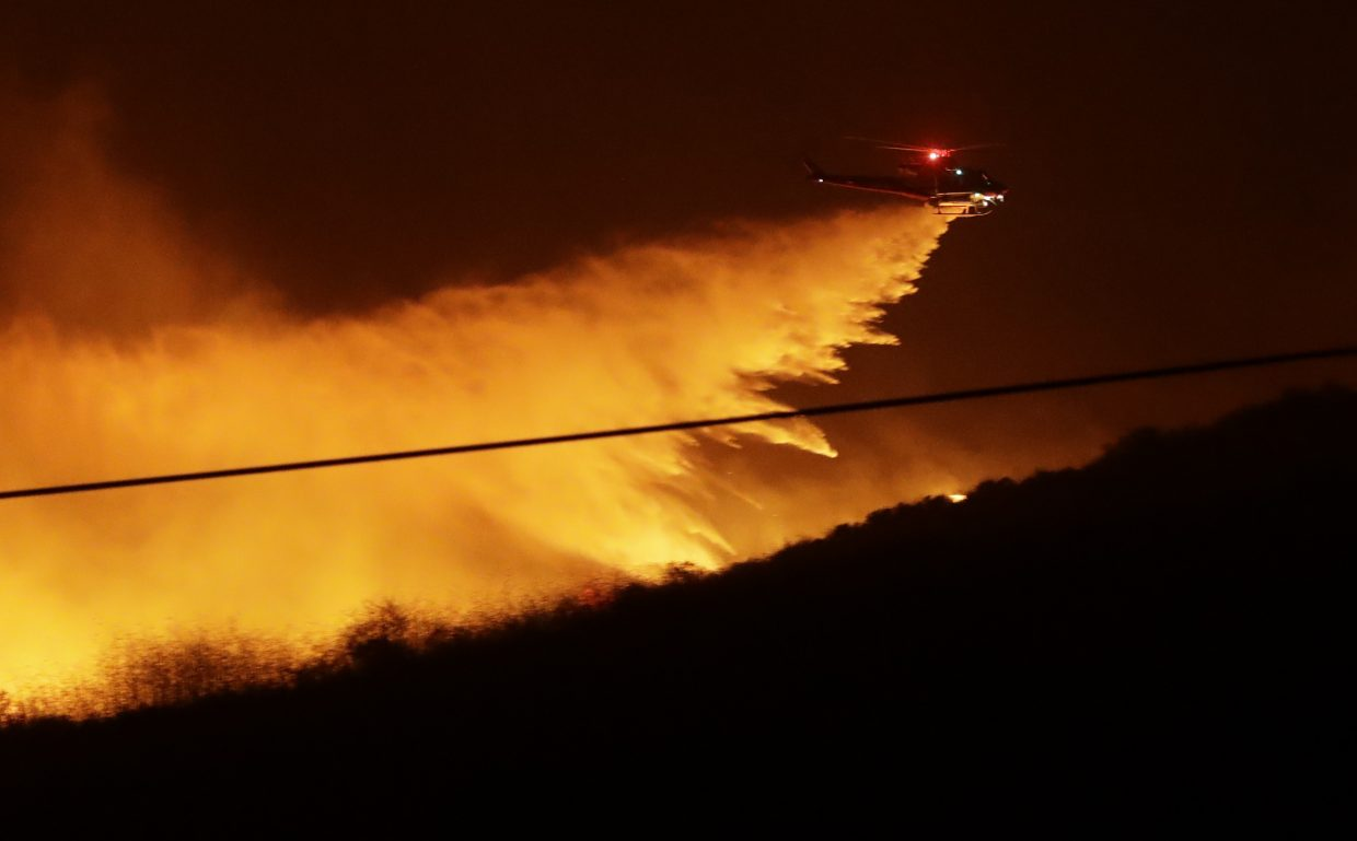 A helicopter drops water on a wildfire Thursday, Dec. 7, 2017, in Bonsall, Calif. The wind-swept blazes have forced tens of thousands of evacuations and destroyed dozens of homes in Southern California.