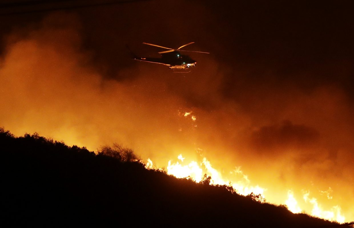 A helicopter flies over a wildfire Thursday, Dec. 7, 2017, in Bonsall, Calif. The wind-swept blazes have forced tens of thousands of evacuations and destroyed dozens of homes in Southern California.