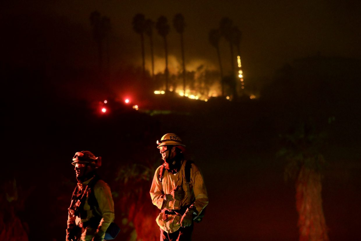 Fire crews look on as they fight a wildfire Thursday, Dec. 7, 2017, in Bonsall, Calif. The wind-swept blazes have forced tens of thousands of evacuations and destroyed dozens of homes in Southern California.