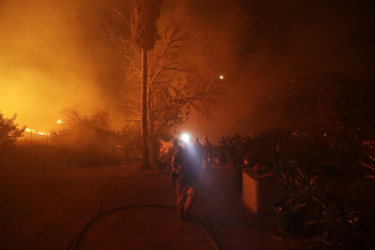 Fire crews prepare to defend a home as a wildfire advances Thursday, Dec. 7, 2017, in Bonsall, Calif. The wind-swept blazes have forced tens of thousands of evacuations and destroyed dozens of homes in Southern California.