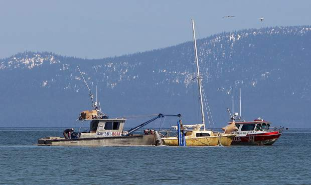 A team with TowBoatU.S. Lake Tahoe floats a sailboat that had been sitting at the bottom of the lake for months.