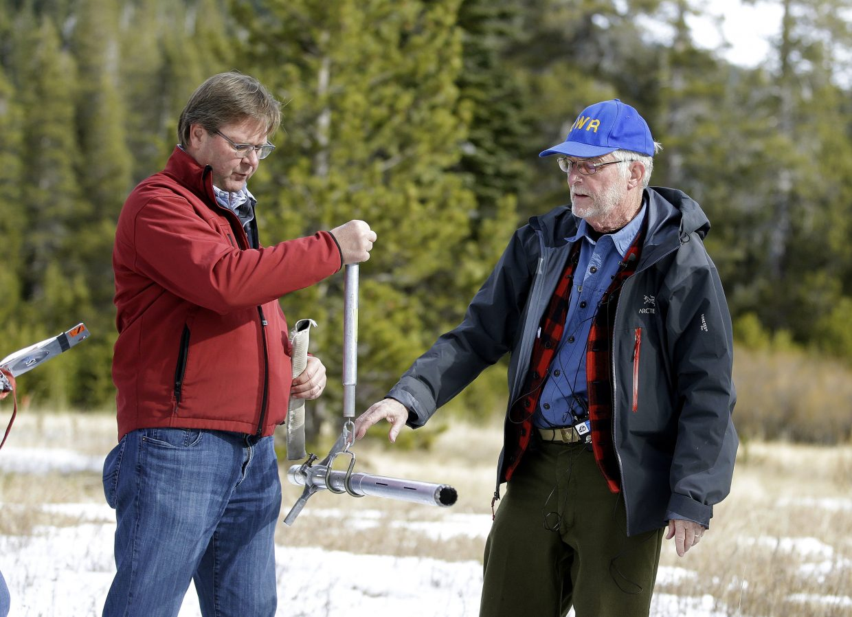 Frank Gehrke, chief of the California Cooperative Snow Surveys Program for the Department of Water Resources, right, checks the weight of the snow survey sample on a scale held by Grant Davis, director of the Dept. of Water Resources, while conducting the first snow survey of the season at the Phillips Station snow course, Wednesday, Jan. 3, 2018, near Echo Summit, California.