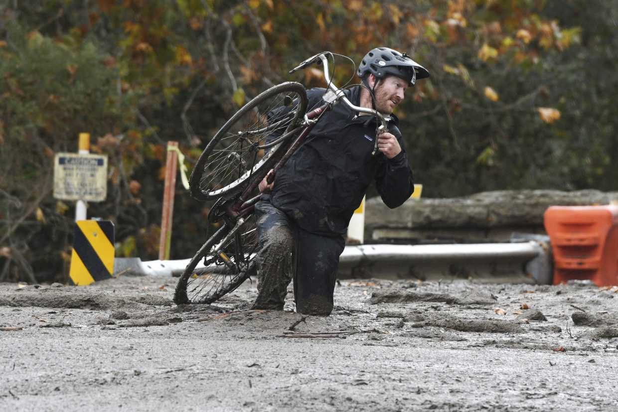 Carpinteria resident Jeff Gallup carries his bike through mud on Foothill Road in Carpinteria, California, Tuesday, Jan. 9, 2018.