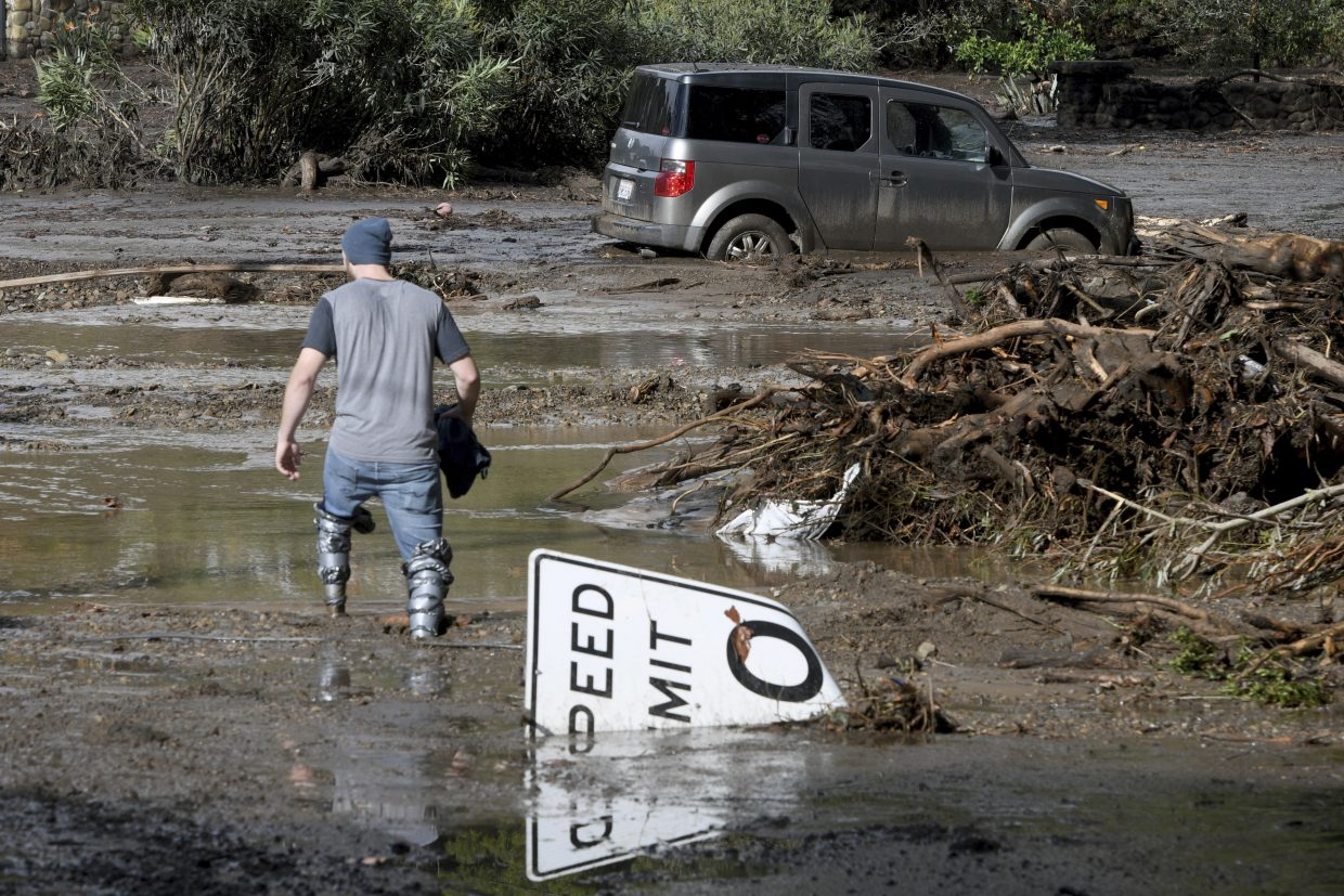 Mitchell Barrett crosses mud from an overflown creek on Sheffield Drive in Montecito, California, following the heavy rain, Tuesday, Jan. 9, 2018.