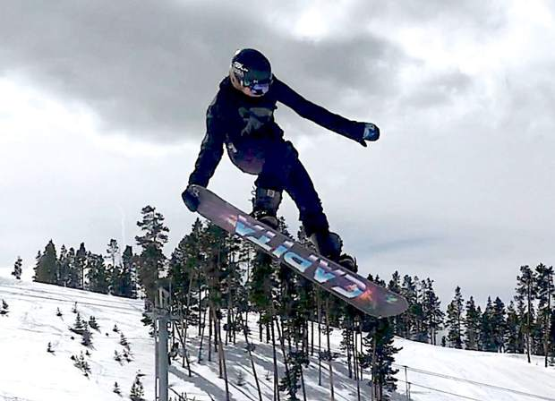Venture Bruner, 14, grabs her snowboard during a jump.