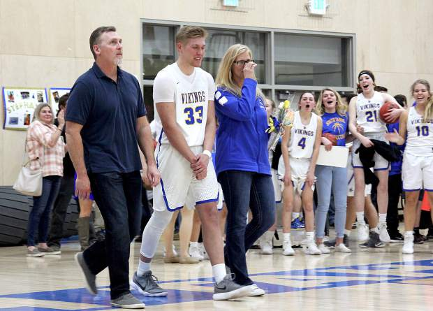 South Tahoe's McCallan Castles and his parents are cheered on by the Lady Vikings basketball team Tuesday, Feb. 7, during senior night.