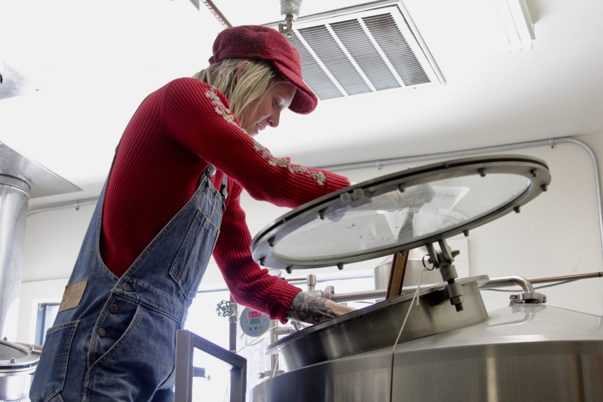 Brigid Campbell stirs the batch of beer that she and other female employees of Cold Water Brewery prepared on International Women's Day.