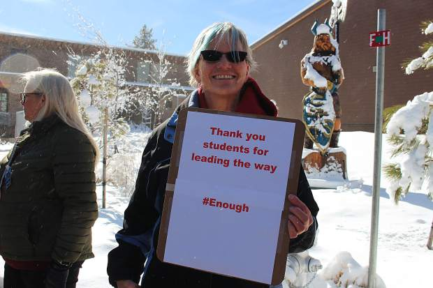 Dr. Kelly Shanahan holds a sign of support for the high school students.