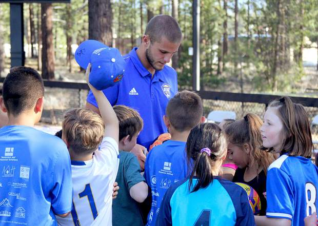 A Reno 1868 FC player signs autogrpahs for kids.