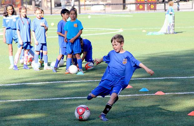 A camper fires a shot on goal after dribbling through plastic cones.