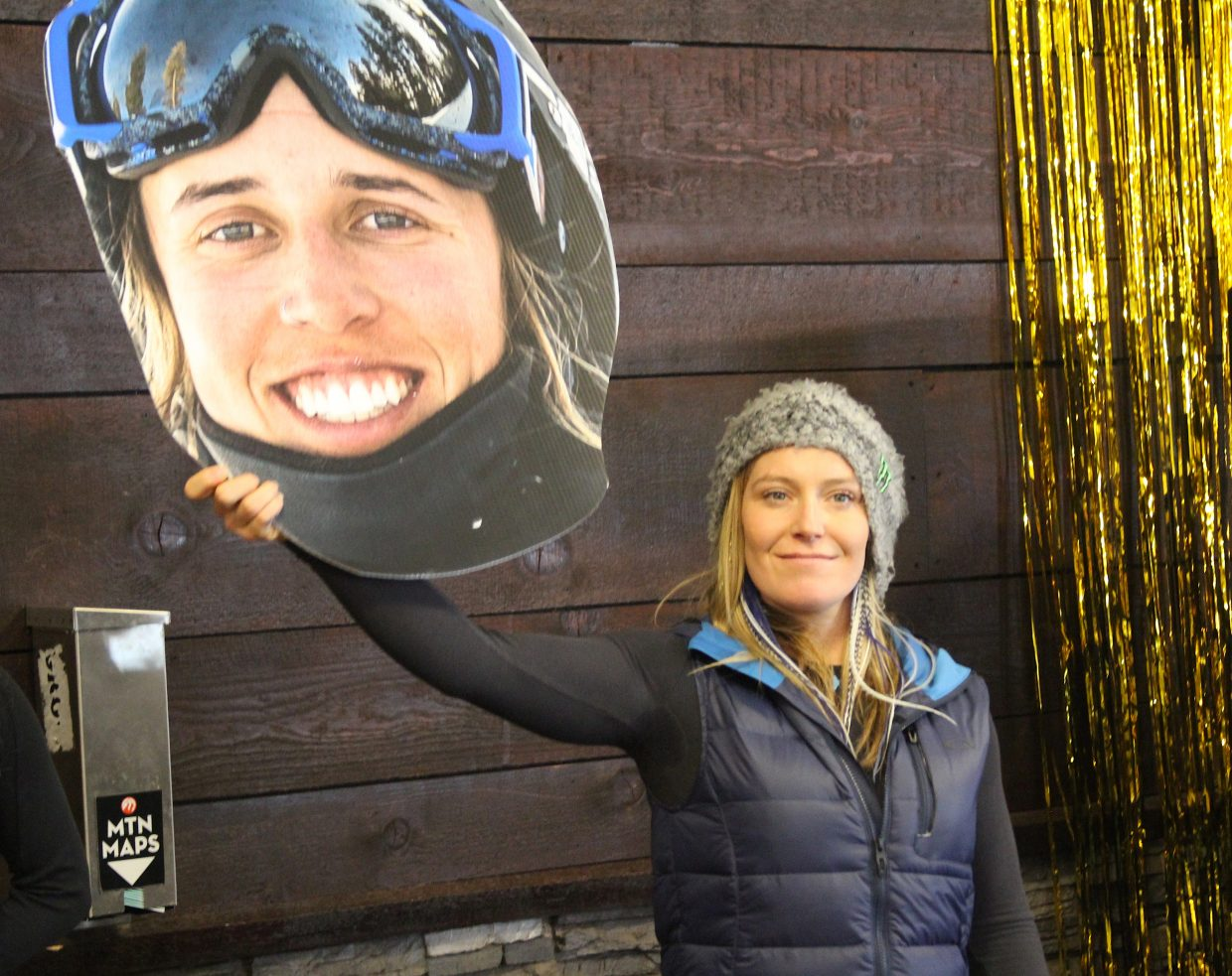 Jamie Anderson holds a cardboard cutout of fellow Olympian Maddie Bowman during the ceremony.