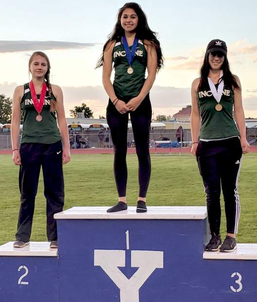 Incline freshman Millie Jenkins stands atop the podium for winning the long jump. she is surrounded by second and third-place teammates Emma Perrell (left) and Belle Johnson.