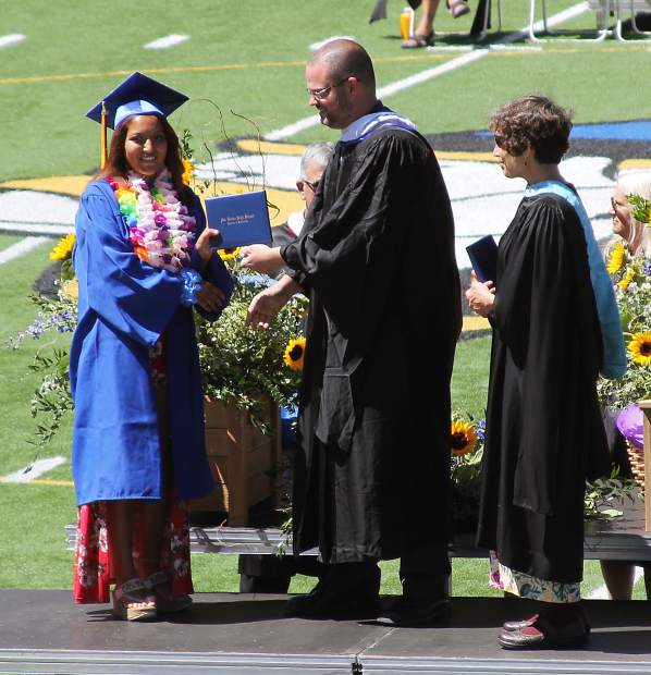 A student receives her diploma at Friday's graduation.