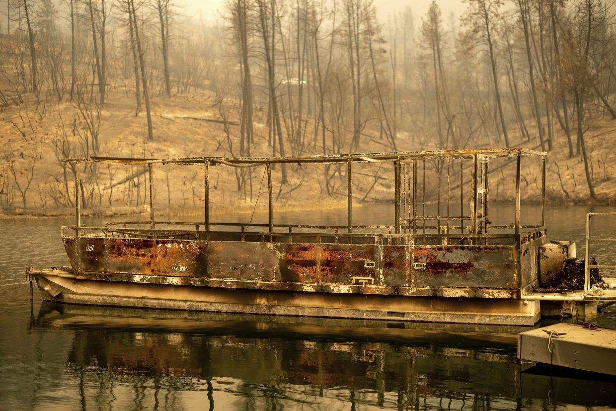 A boat scorched by the Carr Fire floats on Whiskeytown Lake in Whiskeytown, Calif., on Friday, July 27, 2018. The fire rapidly expanded Thursday when erratic flames swept through the historic Gold Rush town of Shasta and nearby Keswick, then cast the Sacramento River in an orange glow as they jumped the banks into Redding.
