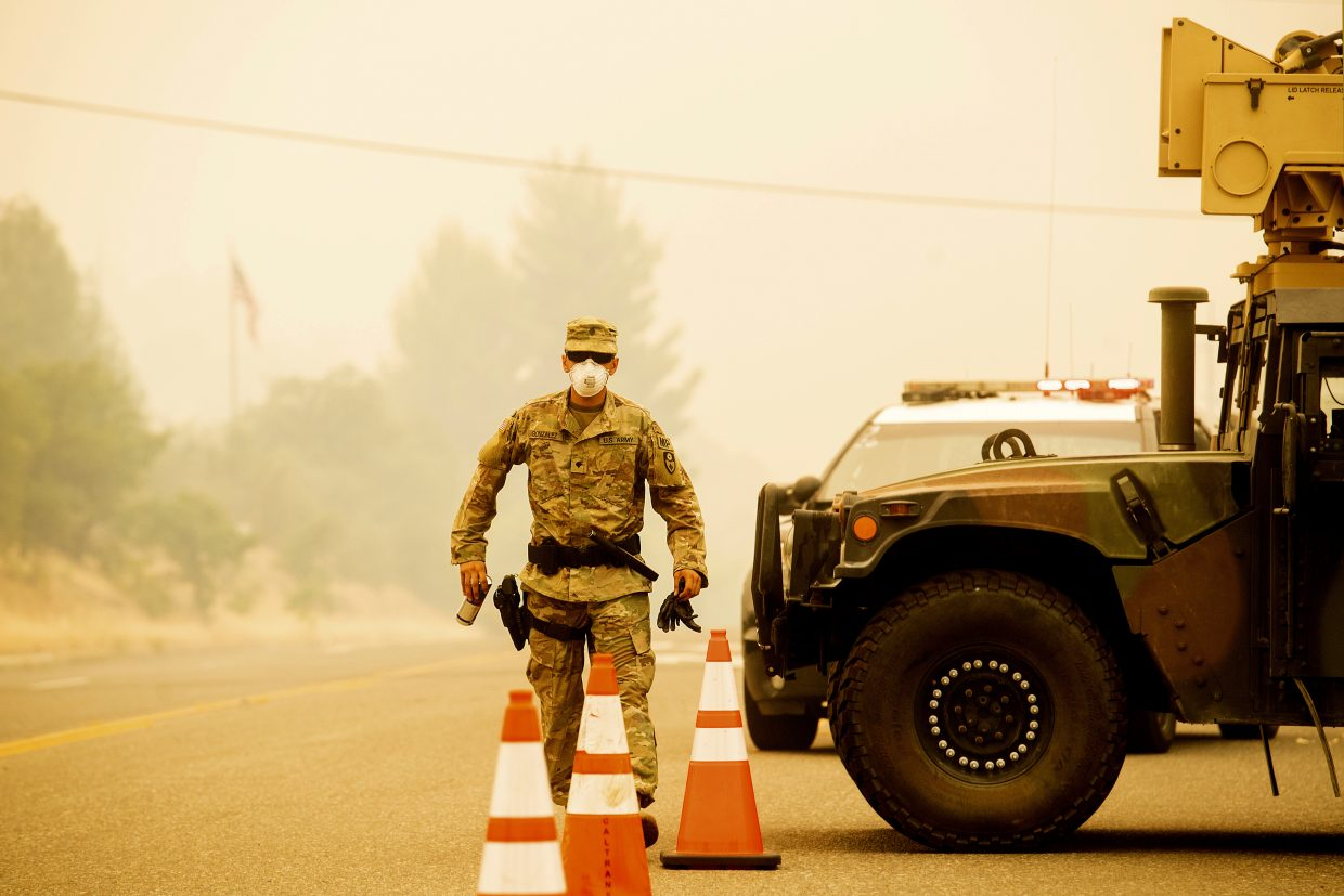 Army National Guard Specialist Gonzalez mans a checkpoint as the Carr Fire burns in Redding, Calif., on Saturday, July 28, 2018. Thousands of residents remain evacuated as the blaze, which has killed multiple people, threatens homes in Redding and surrounding communities.
