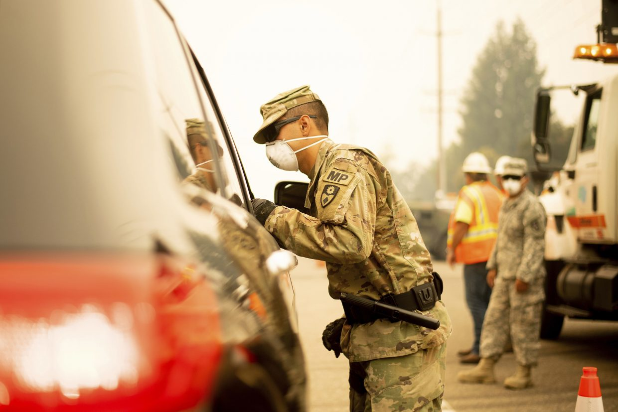 An Army National Guard specialist speaks to a driver at a checkpoint as the Carr Fire burns in Redding, Calif., on Saturday, July 28, 2018. Thousands of residents remain evacuated as the deadly blaze threatens homes in Redding and surrounding communities.
