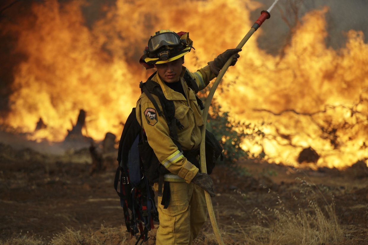 A firefighter makes a stand in front of an advancing wildfire as it approaches a residence Saturday, July 28, 2018, in Redding ,Calif.