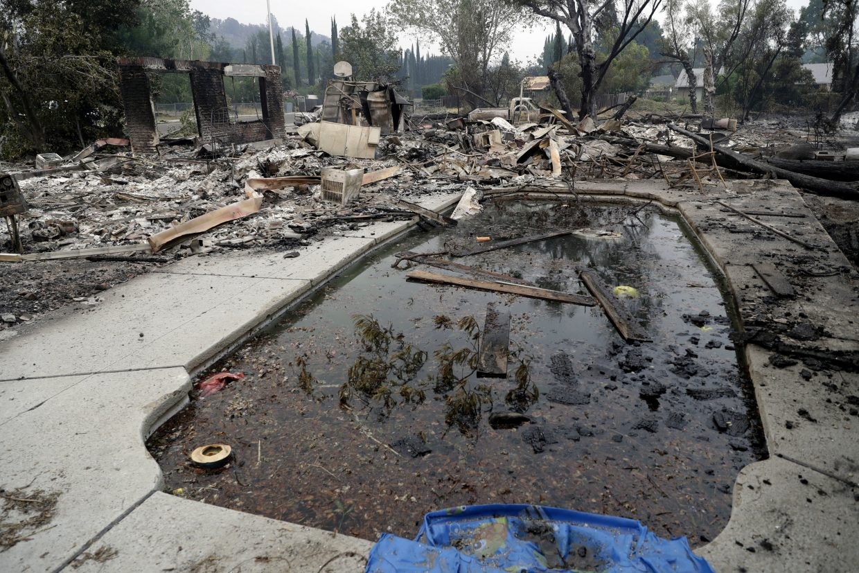 Debris and charred items litter a wildfire-ravaged home Saturday, July 28, 2018, in Redding, Calif.