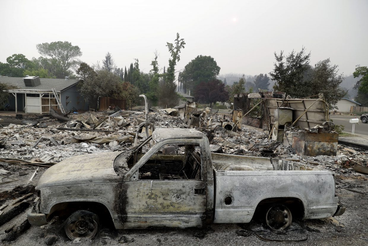 A burned out vehicle sits in front of a wildfire-ravaged home Saturday, July 28, 2018, in Redding, Calif.