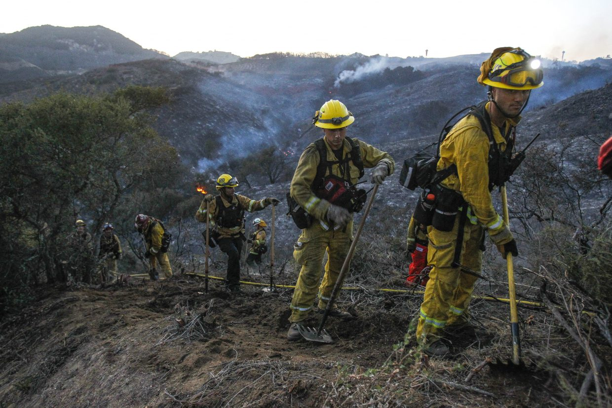 A hand crew of firefighters from various San Diego County fire departments scratch out a fire line after a brushfire burned in De Luz, Calif., on Saturday, July 28, 2018.