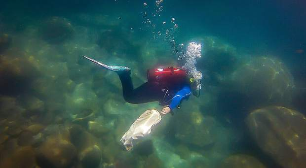 A diver collects trash under the surface of Lake Tahoe.