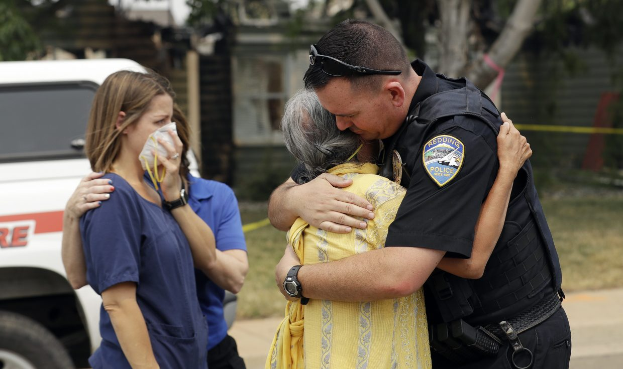 Redding Police Dept. officer Brian Berg, right, comforts a resident, center, wishing not to be identified, after she saw her fire-ravaged home for the first time Thursday, Aug. 2, 2018, in Redding, Calif.