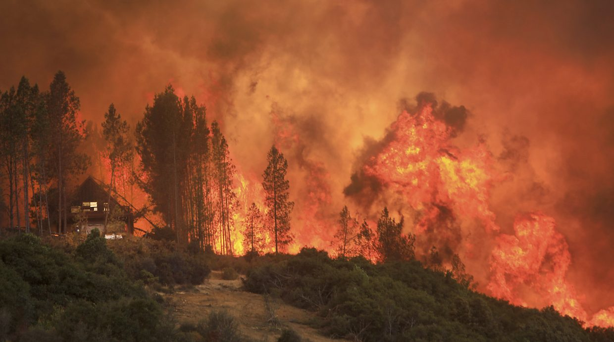 Flames from a wildfire advance up a ridge, towering over a home that eventually burned, Thursday, Aug. 2, 2018, near Lakeport, Calif.