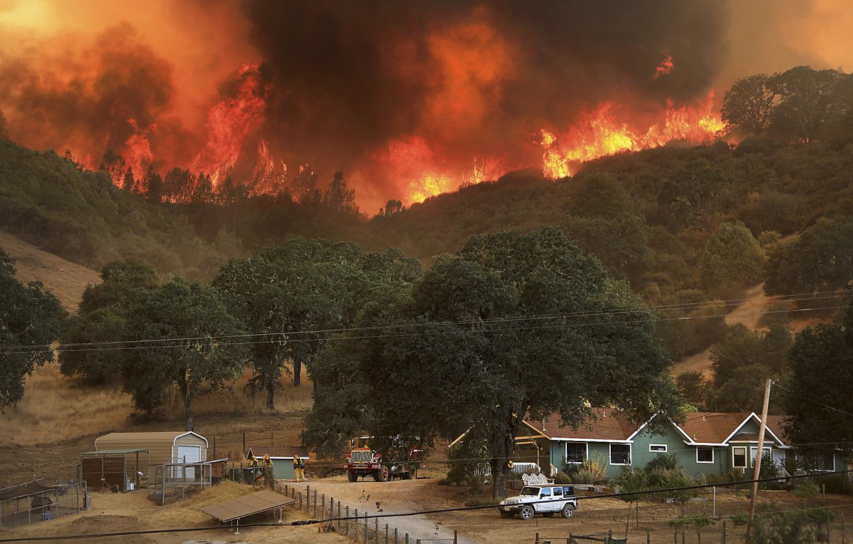 Flames from a wildfire advance down a hillside, towering over homes off Scotts Valley Road, Thursday, Aug. 2, 2018, near Lakeport, Calif.